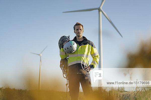 Techniker  der mit Kletterausrüstung auf einem Feld in einem Windpark steht