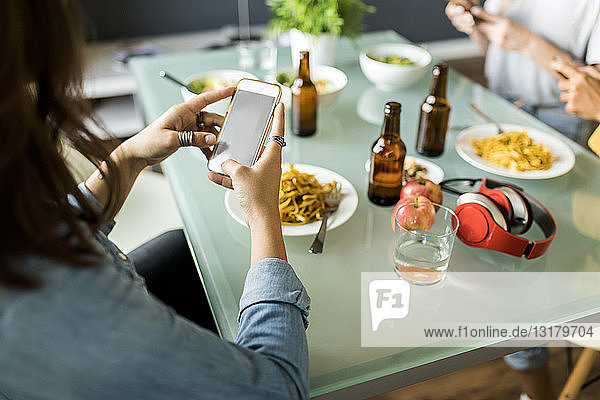 Close-up of friends sitting at table using cell phones