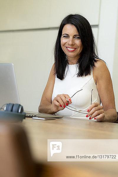 Porträt einer lächelnden dunkelhaarigen Frau mit Laptop am Schreibtisch