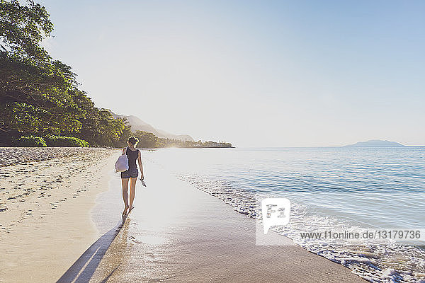 Seychellen  Mahe  Beau Vallon Beach  Frau  die bei Sonnenuntergang am Strand spazieren geht