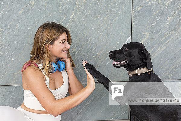 Glückliche junge Frau mit ihrem schwarzen Hund