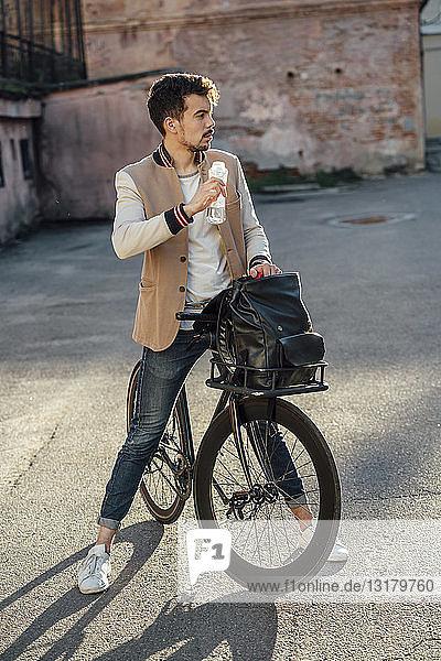 Junger Mann mit Pendler-Fixie-Fahrrad macht auf einem Hinterhof in der Stadt eine Pause
