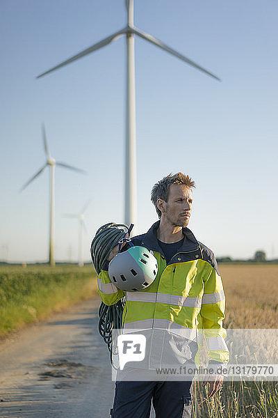 Techniker  der mit Kletterausrüstung auf einem Feldweg an einem Windpark steht