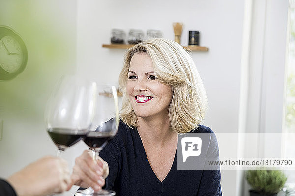 Portrait of smiling blond mature woman toasting with red wine at home