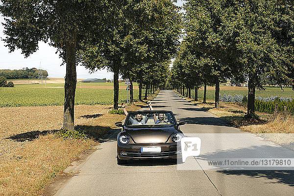 Glückliches Paar fährt in einem Cabriolet auf einer Landstraße