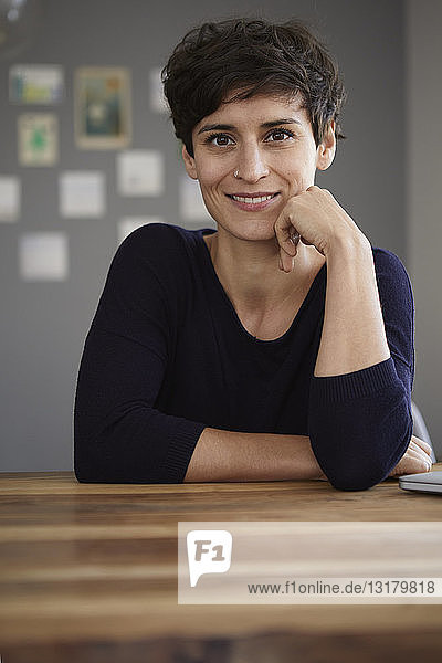 Portrait of smiling woman sitting at table at home