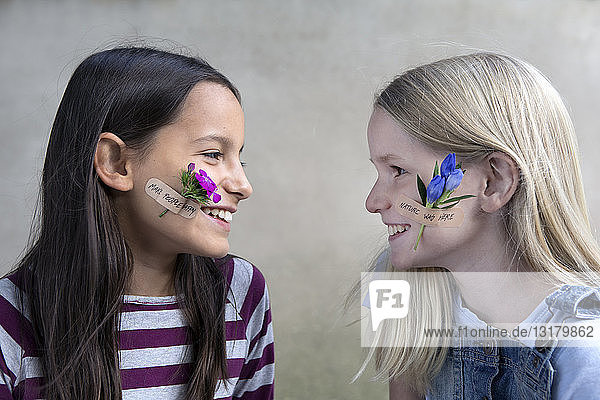 Two smiling girls with flower heads on their cheeks