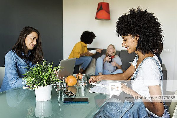 Women using laptop and notebook at dining table with friends in background