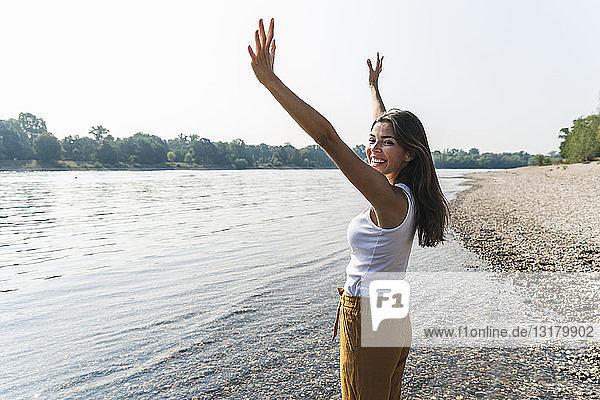 Glückliche junge Frau steht am Flussufer und hebt ihre Arme