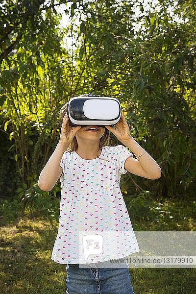 Amazed little girl wearing Virtual Reality Glasses in the garden