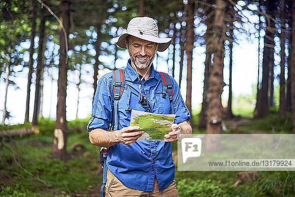 Smiling man looking at map during a hike in the forest