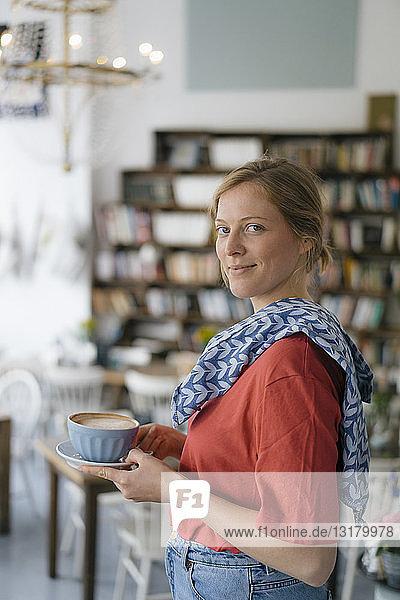 Porträt einer lächelnden jungen Frau  die in einem Café Kaffee serviert