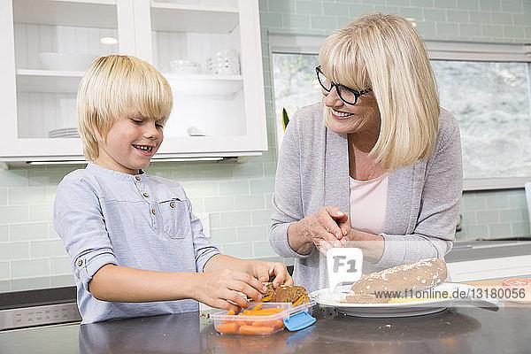 Großmutter und Enkel bereiten gemeinsam eine Lunchbox in der Küche vor