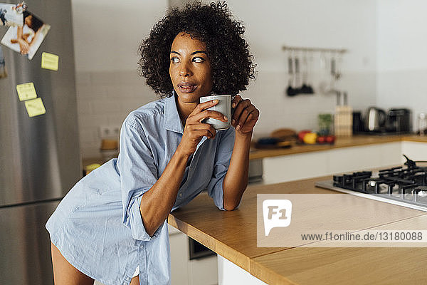 Woman standng in her kitchen  having her morning coffee