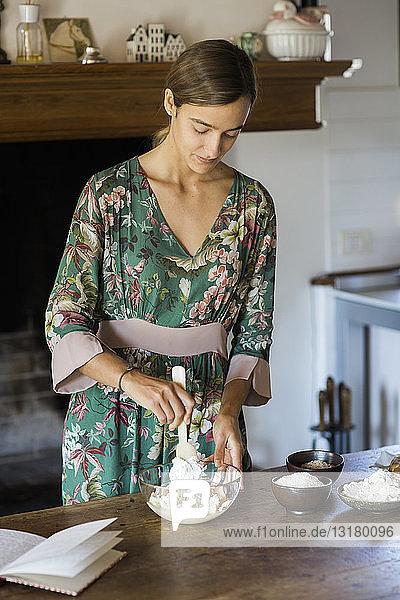 Young woman preparing cake dough