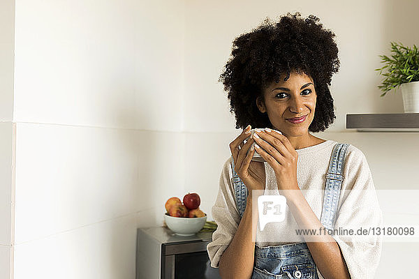 Portrait of smiling woman holding cup in kitchen at home
