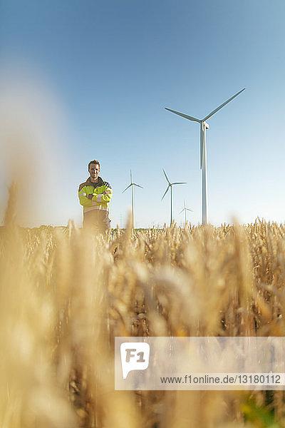 Porträt eines lächelnden Ingenieurs  der auf einem Feld in einem Windpark steht