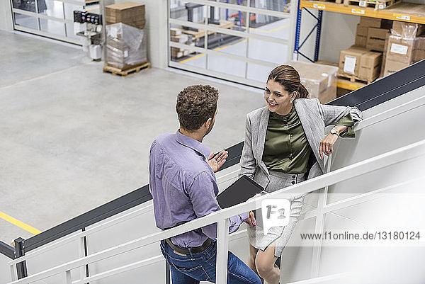 Geschäftsmann und -frau stehen in Gesellschaft auf einer Treppe und unterhalten sich