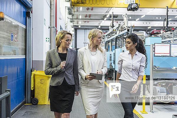 Drei Frauen mit Tabletten gehen und sprechen in der Fabrikhalle