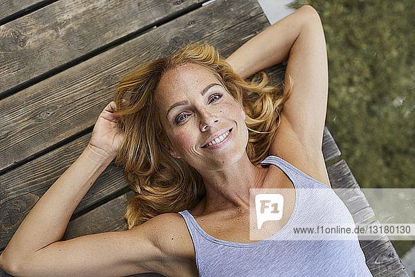 Porträt einer lächelnden blonden Frau  die auf einem Holzsteg an einem See liegt