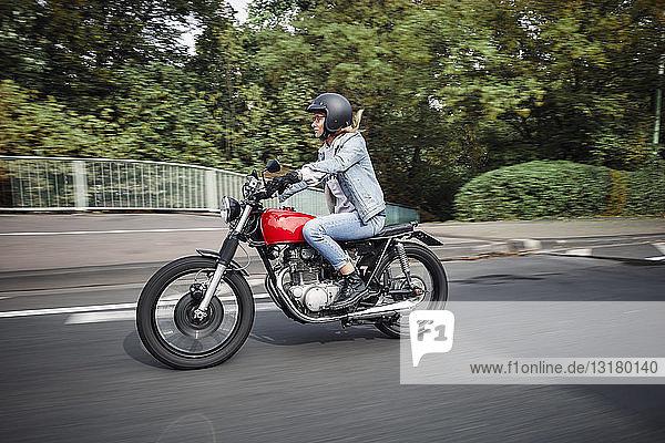Junge Frau fährt Motorrad auf einer Straße