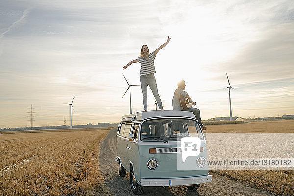 Glückliches Paar mit Gitarre auf dem Dach eines Wohnmobils in ländlicher Landschaft