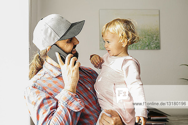 Father holding his little daughter on his arm  while talking on his smartphone