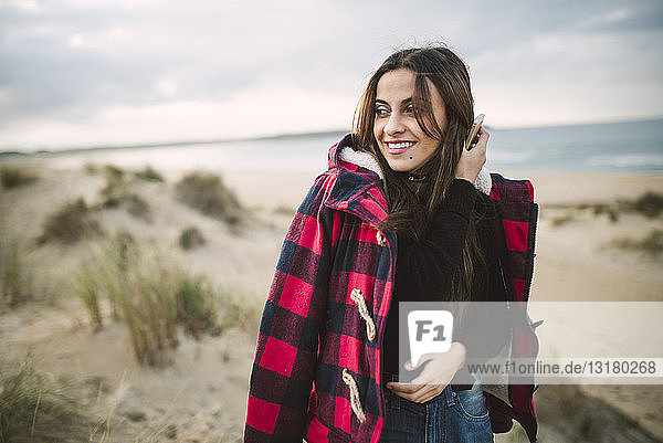 Portrait of smiling woman with cell phone on the beach