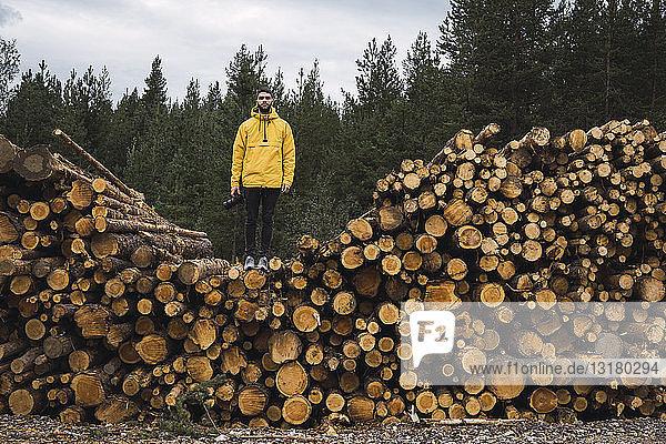Mann mit Kamera auf Holzstapel stehend