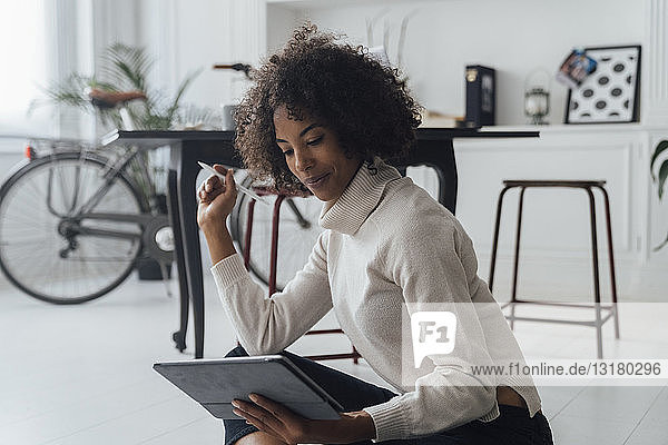 Disigner sitting on ground of her home office  using digital tablet