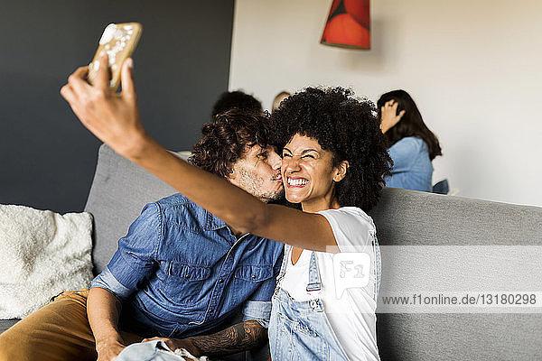 Glückliches Paar  das auf der Couch sitzt und ein Selfie