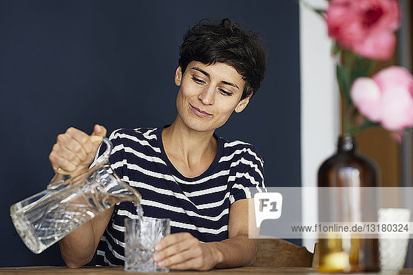 Woman at home sitting at wooden table pouring water into glass