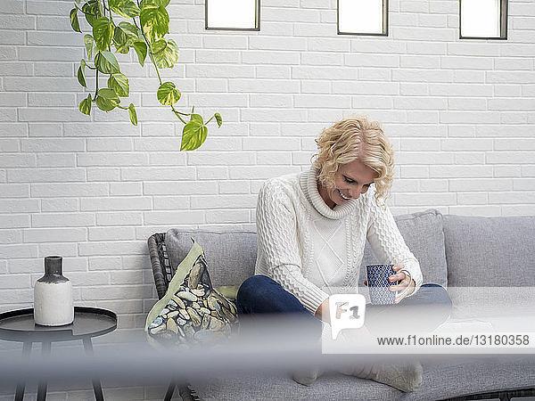 Lächelnde reife Frau sitzt zu Hause auf der Couch und hält Kaffeetasse