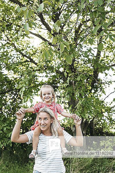 Glückliche Mutter trägt Tochter huckepack in der Natur