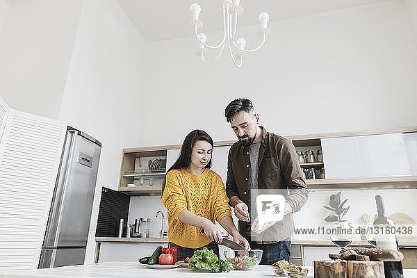 Couple preparing salad together in modern kitchen
