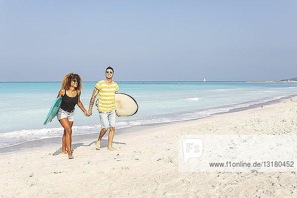 Paar  das am Strand spazieren geht und Surfbretter trägt