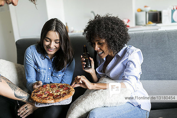 Tattooed man offering pizza to friends sitting on couch
