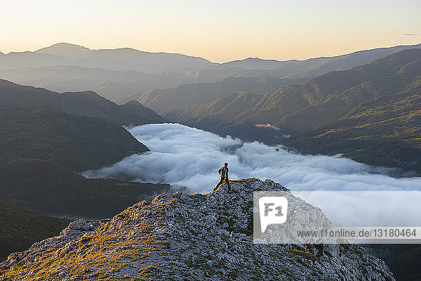 Italy  Umbria  Sibillini National Park  hiker on viewpoint at sunrise
