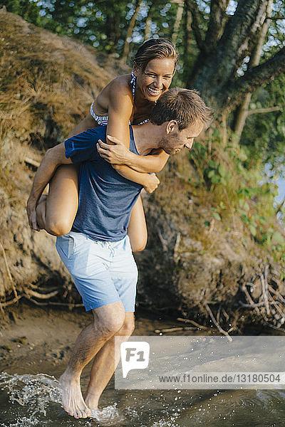 Glücklicher Mann trägt seine Freundin huckepack an einem See