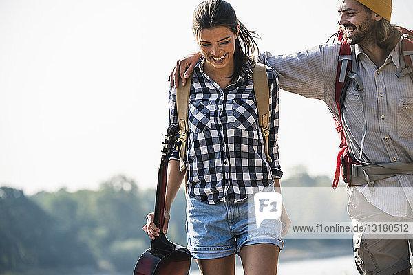 Glückliches junges Paar mit Rucksäcken und Gitarre im Freien
