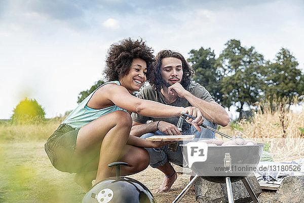 Glückliches Paar beim Grillen in der Natur Glückliches Paar beim Grillen in der Natur