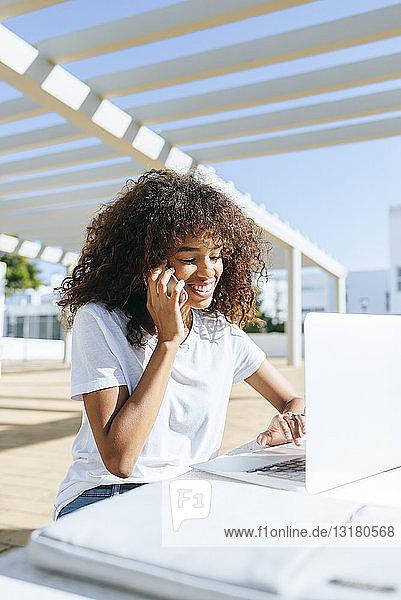 Lächelnde junge Frau am Telefon  die mit einem Laptop am Tisch sitzt