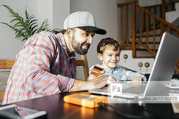 Father and son using laptop together  online shopping