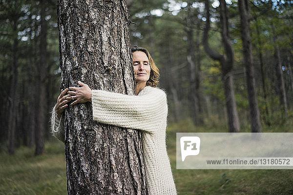Frau umarmt Baum im Wald