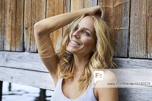 Lächelnde blonde Frau  die sich an eine Holzhütte an einem See lehnt