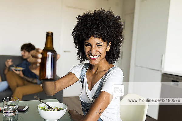 Portrait of smiling woman raising beer bottle at dining table