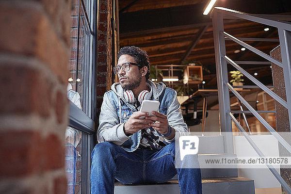 Junger Mann arbeitet in einem kreativen Start-up-Unternehmen und benutzt ein Smartphone