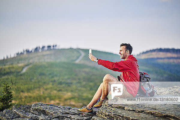 Man sitting on rock taking selfie with his cell phone during hiking trip in the mountains