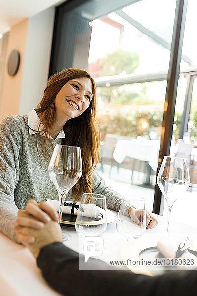 Lächelnde Frau hält in einem Restaurant mit einem Mann Händchen