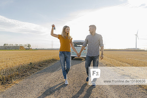 Young couple with car key walking on dirt track at camper van in rural landscape